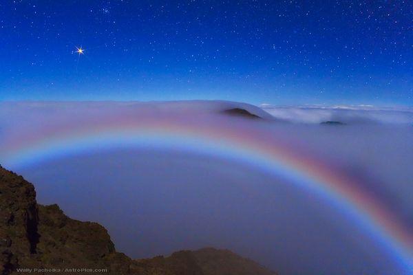 Марс сияет, как ярко-красная звезда над «лунной радугой» вблизи вулкана Халикала на Гавайях. «Лунная радуга» появляется, когда лунный свет проходит через крошечные капельки воды