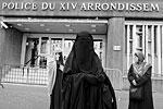 Найет в бурке и Кенза Дридер в никабе (сзади слева), после освобождения из полицейского участка в Париже, куда их доставили за ношение этой одежды