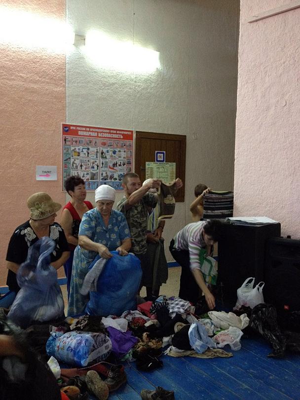 Жители в администрации города Крымска выбирают одежду, привезенную волонтерами