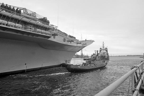 Буксиры подводят гигантский корабль к месту стоянки
