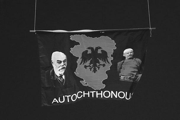 Изначально сообщалось, что к летательному аппарату был привязан флаг, а позже появилось уточнение, что это политический баннер с изображением карты «Великой Албании», а также Исы Болетения и Ислаила Джемалия, которые первые в 1912 году подняли албанский флаг