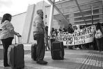 Пассажиры стоят перед входом в аэропорт в Морелии, заблокированный демонстрантами, которые держат плакат с надписью: «Я есть и буду студент, в оппозиции угнетающему правительству, ENE (педагогический колледж, где учились пропавшие студенты) живет!»  (фото: Reuters)
