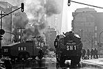 В центре города чувствуется сильный запах гари: специальные машины тушат горящие автомобили, которые подожгли протестующие (фото: Reuters)