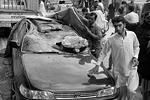 Люди стоят возле автомобиля, поврежденного в результате землетрясения в Пешаваре (Пакистан) (фото: Mohammad Sajjad/AP Photo/ТАСС)