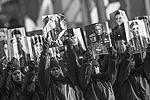 Молодые ребята держат фотографии участников того исторического парада 7 ноября 1941 года (фото: Станислав Красильников/ТАСС)