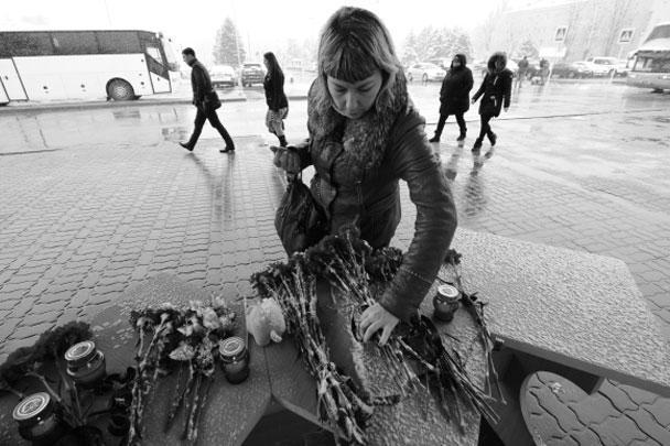Женщина возлагает цветы у аэропорта Ростова-на-Дону, где при посадке разбился пассажирский самолет из Дубая