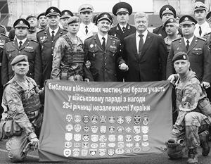 Украинские военные, стоящие рядом с Порошенко, демонстрируют флаг с эмблемами воинских частей и свою новую военную форму