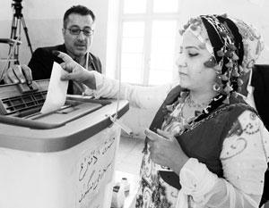 Голосующие курды находят свою фамилию в списке и ставят напротив отпечаток большого пальца, предварительно смазанного краской