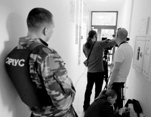 Охранник и журналисты у офиса РИА «Новости Украина» в Киеве, где СБУ проводит обыски