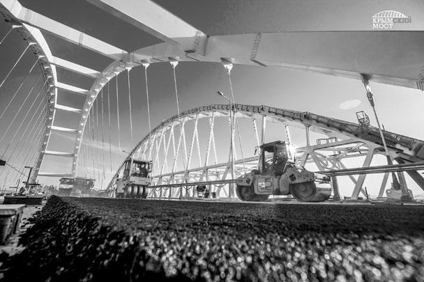 На автодорожной арке Крымского моста строители начали укладку асфальтобетона. На данный момент нижний слой уже готов, верхний уложат через несколько дней – после технологического перерыва. В целом дорожное покрытие пролета будет двухслойным с толщиной в 11 см