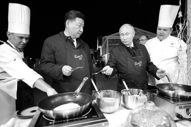 В выставочном павильоне «Русские морепродукты и русский рынок» Путин и Си Цзиньпин надели фартуки и приготовили блины