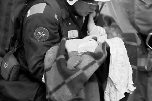 Подполковник Петр Гриценко выносит младенца из-под завалов