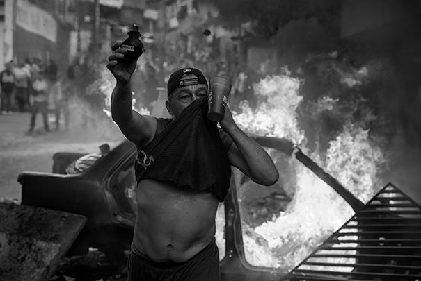 Один из участников протеста показывает шумовую гранату, которую спецслужбы использовали для разгона толпы революционеров