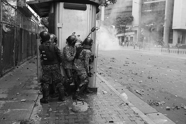 На некоторых улицах Каракаса идут настоящие бои, правоохранителям приходится укрываться от агрессии многотысячной толпы