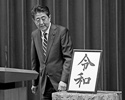 Премьер Синдзо Абэ с иероглифами «рэй» и «ва» (фото: AP Photo/Eugene Hoshiko/ТАСС)
