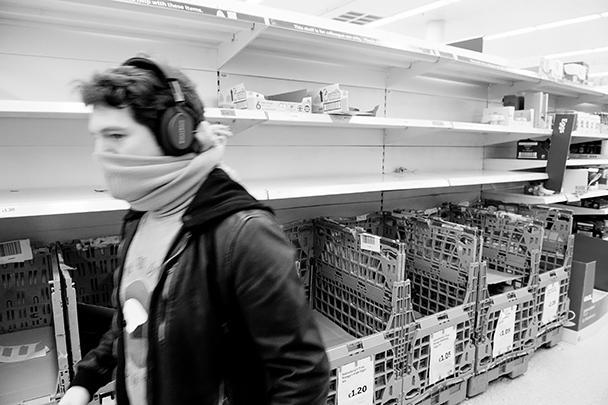 Британский покупатель с импровизированной маской на лице возле пустых полок с молочными продуктами в лондонском магазине Sainsburys. Продажи жизненно важных товаров и медицинских средств распределяются по лондонским магазинам определенными партиями, чтобы избегать дефицита