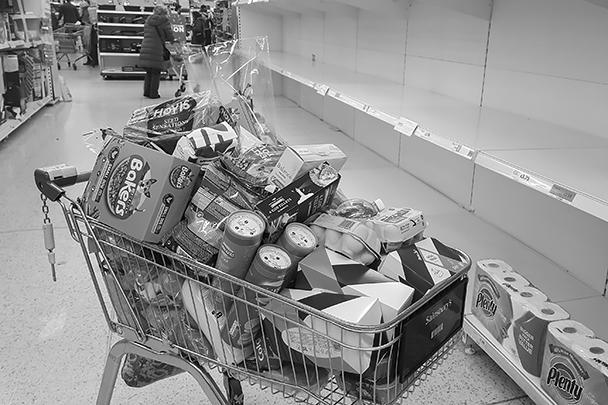 Тележка полна покупок, так как в очередном лондонском магазине заканчивается туалетная бумага на фоне возросшего числа случаев заражения коронавирусом