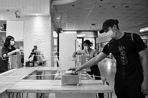 Мужчина забирает свой кофе. Кафе в одном из торговых центров Бангкока ввело практику «бесконтактной» выдачи заказов