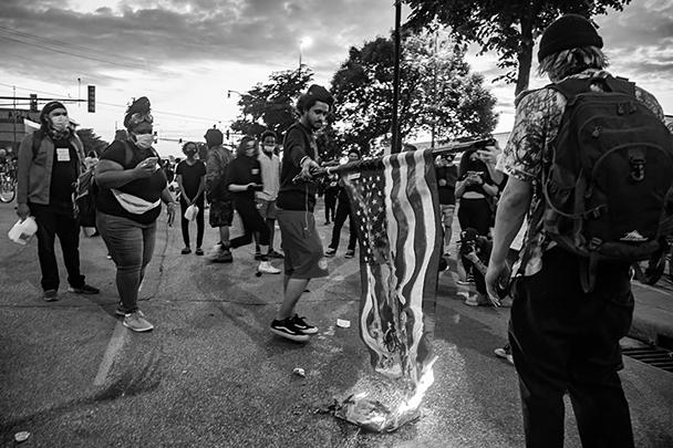 В окружении полиции протестующие сожгли американский флаг