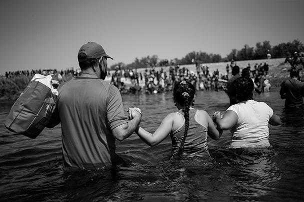 На фото - мигранты пересекают реку Рио-Гранде, чтобы попасть из Мексики в США