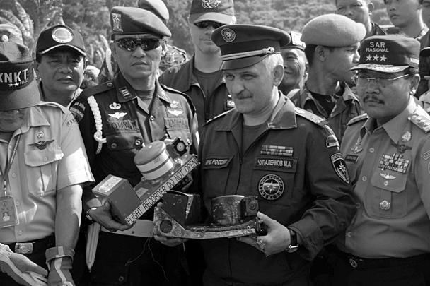 Руководитель оперативной группы МЧС РФ в Индонезии Михаил Чупаленков (в центре) продемонстрировал найденный речевой регистратор, который очень сильно обгорел