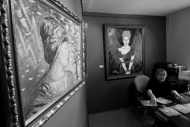 Директор галереи «Экспо-88» Елена Яковлева у картин «Анна Ахматова» и «Жертва» (слева направо) обвиняемой по делу Оборонсервиса Евгении Васильевой, представленных на ее персональной выставке «Цветы из неволи»
