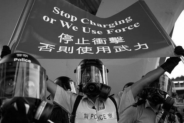 Полицейский держит плакат «Прекратите накалять обстановку, иначе мы применим силу» – официальное предупреждение властей Гонконга к протестующим