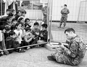Эта фотография уже стала знаменитой – американский военный играет эвакуированным афганским детям на военной базе Рамштайн в Германии