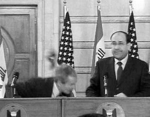 Буш увернулся от обоих ботинков, и они попали в стену рядом с американским и иракским флагами