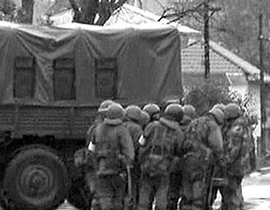 Возле перекрывших улицы грузовиков дежурят вооруженные люди