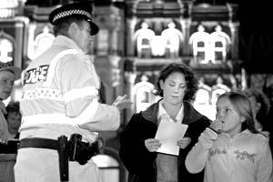 Офицер британской полиции раздает памятки с правилами личной безопасности жителям Ипсвича