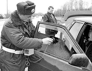 Инспектор проверяет тонировку стекол автомобиля на соответствие ГОСТу