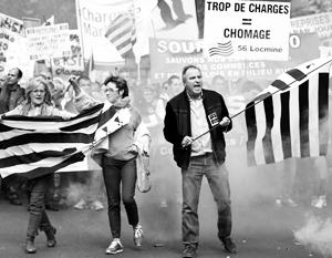 Французские безработные бастуют на улицах Парижа. Надпись на баннере: «Слишком большие налоги равны безработице»