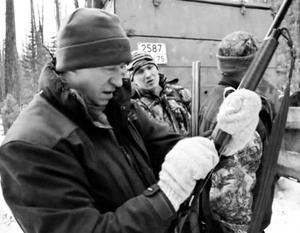 Человек, похожий на губернатора, сперва пристреливает ружье, а потом в упор убивает спящего медведя