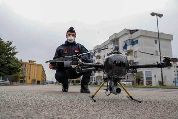 Полиция по всему миру несет службу в особом режиме из-за коронавируса. В то время, как в странах Европы, Азии и Латинской Америки обычные люди обязаны сидеть на карантине, стражи порядка следят за его исполнением. В Италии правоохранителям помогают дроны. Например, этот беспилотник сопровождает полицейского в Неаполе