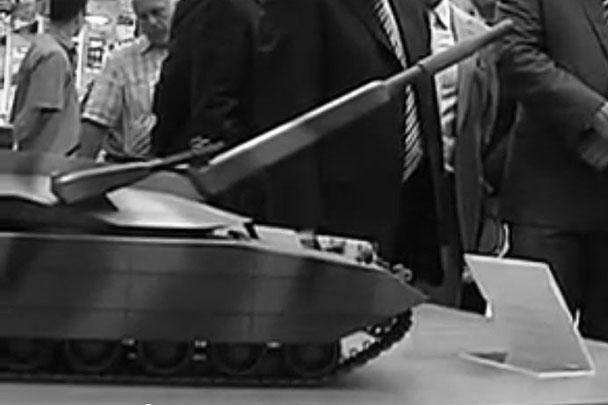 Модели новейших образцов бронетанковой техники, которые уже в ближайшее время будет выпускать Россия, случайно удалось заснять одной из региональных телекомпаний. Внешний вид этой техники опубликован впервые. На этом фото – предполагаемая модель основного боевого танка на платформе «Армата», который должен поступить на вооружение в 2015 году
