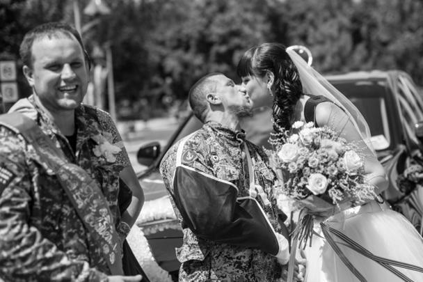 Один из самых известных ополченцев ДНР под позывным Моторола сыграл свадьбу в Донецке. Это первый официальный брак, заключенный в Новороссии. Торжество посетили первые лица республики, а белое платье невесты украшала кобура